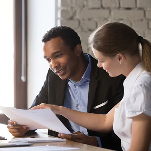 man and woman in professional setting looking at paperwork